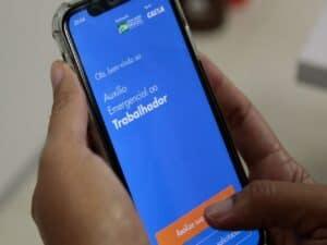 usuário segurando smartphone com tela aberta no aplicativo do auxílio emergencial representando nova prorrogação do auxílio emergencial