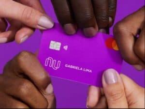 4 mãos segurando um cartão roxinho do Nubank, que se tornou a 5ª maior instituição financeira