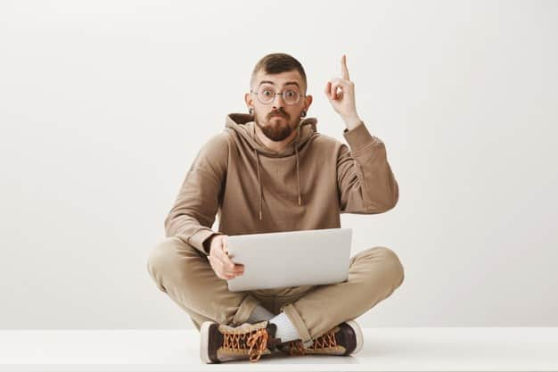 rapaz com computador no colo aponta para cima indicando ter objetivos claros na sua estratégia de investimento