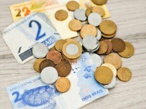 notas de 2 e de 20 reais e várias moedas jogadas sobre uma mesa, representando orçamento do fgts 2021