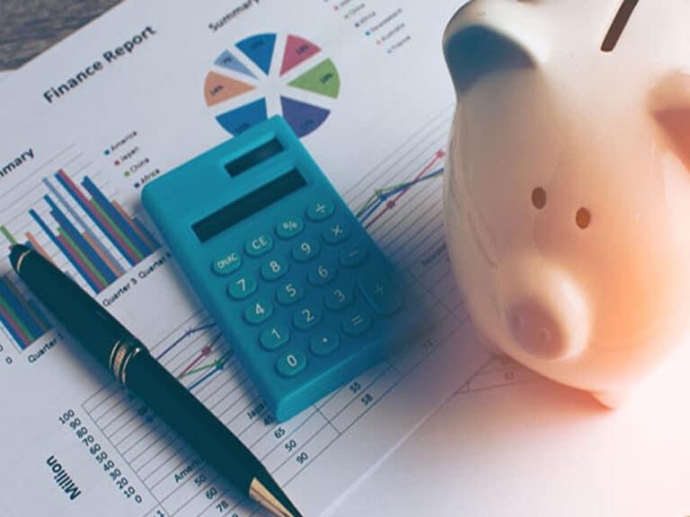 cofrinho de porco ao lado de calculadora, representando produtos de renda fixa