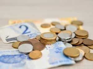 notas de 2 e 20 reais e várias moedas em cima delas, representando reajuste residual do salário mínimo 2021