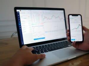 tela de computador e celular mostrando gráficos de ativos de renda variável