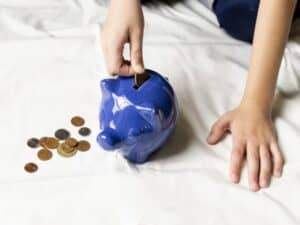 criança coloca moedas em um cofre azul