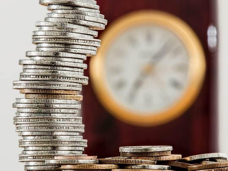 pilha de moedas e relógio, representando rentabilidade da poupanca