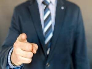 homem de negócios apontando com o dedo indicador representando setores em alta em 2021