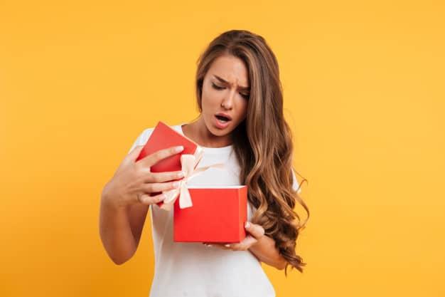 Mulher faz cara de surpresa desagradável ao abrir um presente