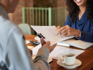 mulher sentada em frente a outra pessoa entrega documentos, representando suspensão do contrato de trabalho