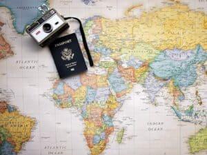 câmera fotográfica e passaporte em cima do mapa do mundo. O governo do Brasil prorrogou para 2022 o prazo de reembolso para viagens