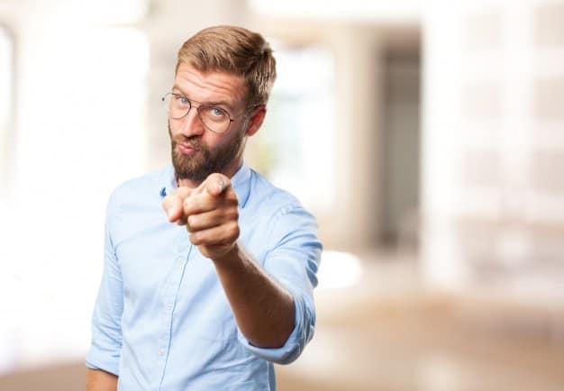 Homem aponta para o leitor indicando que ele está em busca de uma das melhores corretoras de valores para investir bem