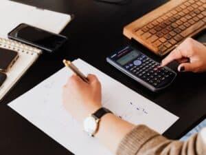 Imagem de uma pessoa usando sua mesa de trabalho com um papel e calculadora para ilustrar o conteúdo da Calculadora de Custo de Funcionário para Empresa