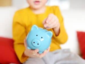 criança colocando dinheiro em um cofrinho