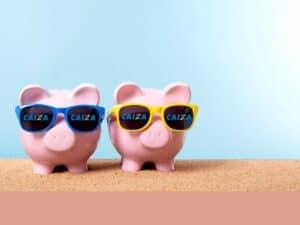 dois cofrinhos em formato de porquinho com óculos de sol com o logotipo caixa
