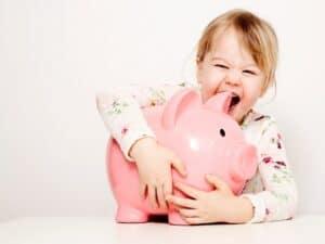 criança abraçando um cofrinho em formato de porco representando conta poupança para menor de idade