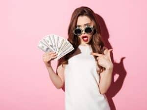 mulher segurando dinheiro em espécie