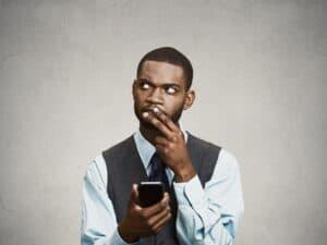 homem segurando o celular com expressão confusa
