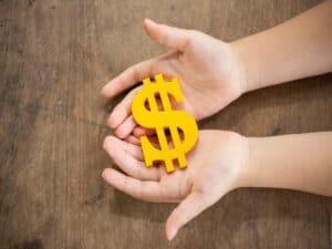 duas mãos seguram um cifrão em amarelo, representando pec do auxílio emergencial