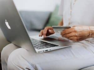 Imagem de uma mulher usando o computador para fazer compras no cartão de crédito, representando o conteúdo que pesquisa se a Wish é confiável