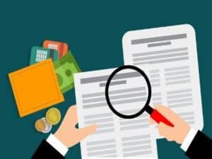 Análise de crédito com uma pessoa avaliando documentos com uma lupa na mão. Carteira, dinheiro e cartões de crédito do lado.