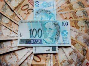 duas notas de 100 reais cruzadas estão em cima de um leque de notas de 50 reais, representando auxílio emergencial 2021
