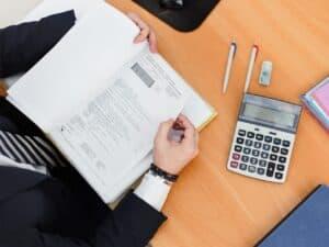 Imagem de uma mesa com calculadoras, canetas e um caderno, representando nosso conteúdo da calculadora de financiamento price