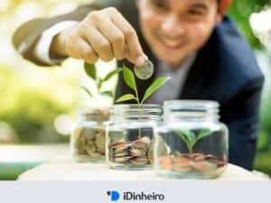 homem colocando moeda em um vidro que contém moedas e plantinhas, representando cdb liquidez diária