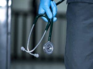 mão com luva segurando estetoscópio representando cobertura obrigatória de planos de saúde