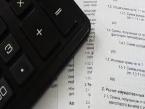 calculadora e documentos representando como declarar empréstimo no IR