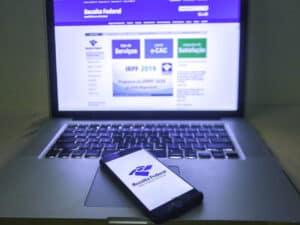 Na imagem, o site da Receita Federal está aberto em um notebook. Um aparelho celular também está com acesso no site da Receita. Em ambos, é possível fazer a declaração pré-preenchida em 2021