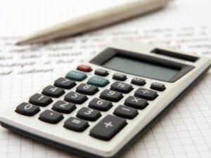calculadora, caneta e papel representando controle de contas a pagar