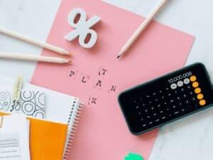 papel, canetas e celular aberto na calculadora, representando declarar imóvel financiado