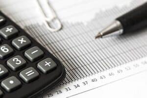 papel com números e uma calculadora, uma caneta e um clips em cima