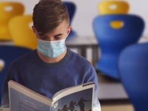 aluno com um livro na mão e sentado na sala de aula com uma máscara no rosto, representando auxílios para estudantes
