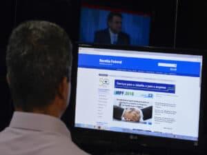 senhor sentado na frente de um computador com a página da Receita Federal aberta, vendo o extrado do ir 2021