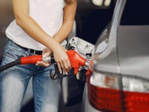 mulher usando calça jeans e blusa branca abastece o carro, representando impostos sobre combustíveis