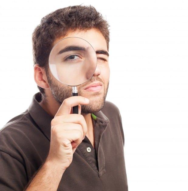 Rapaz olha com uma lupa para fazer seu controle de contas a pagar