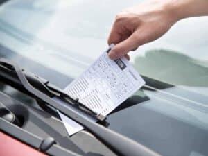 mão recolhendo multas de trânsito de janela de carro