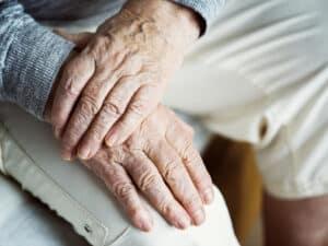 mãos de dois idosos, uma sobre a outra, representando pagamento da aposentadoria