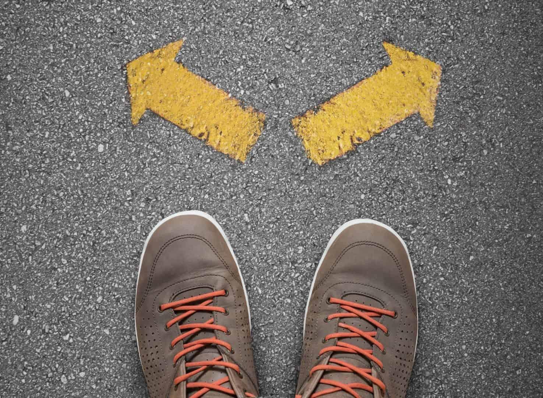 pés de uma pessoa parada em frente à setas apontando em diferentes direções