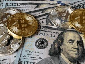 moedas de bitcoin e cédulas de dólar, representando recorde do bitcoin