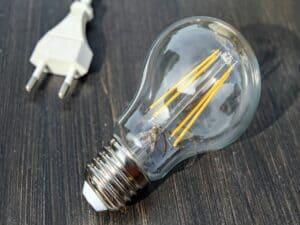 uma lâmpada apagada deitada sobre uma mesa com o cabo de um eletrodoméstico desligado ao lado, representando reajuste na conta de luz