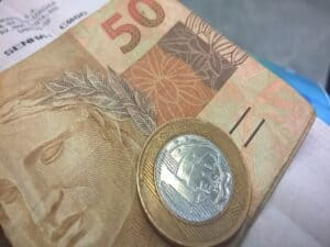 atrás tem uma senha de banco com uma nota de 50 reais em cima e uma moeda de 1 real sobre a nota, representando saque do fgts