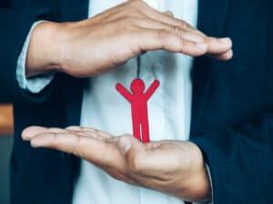 homem vestindo paletó e camisa social coloca uma mão em cima da outra e entre elas há o desenho de uma pessoa na cor vermelha, representando a proteção dos seguros
