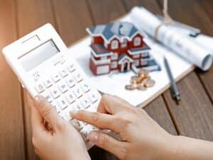 pessoa calcula o valor da inflação de aluguel em março com calculadora. ao fundo, a miniatura de uma casa está em cima de um livro