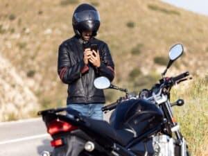 Motoqueiro na beira da estrada, em pé ao lado da moto, mexendo no celular