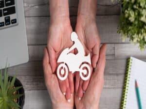 mãos sobrepostas segurando uma imagem de uma pessoa sentada em uma moto