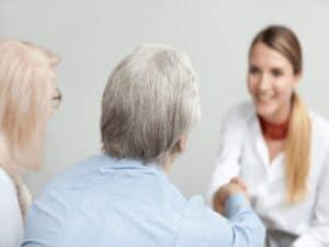 casal de idosos fecha acordo com gerente de banco. ambos aparecem de costas para o espectador, enquanto a gerente está no fundo, em segundo plano. eles discutem o novo limite para empréstimo consignado
