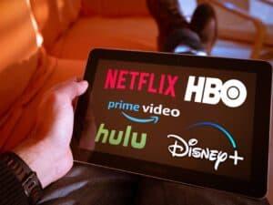 mão segurando tablet com logo de diversos serviços de streaming, que podem ter tributo