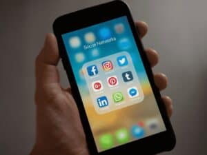 mão segurando celular exibindo aplicativos de redes sociais, representando bloquear telemarketing whatsapp