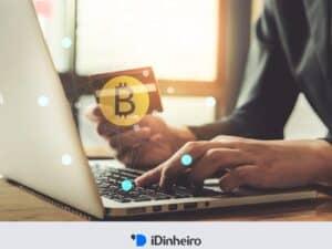 pessoa segurando cartão de crédito em frente ao laptop para comprar bitcoin